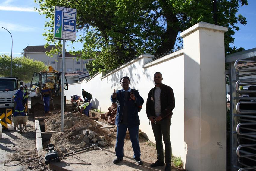 Edward Dywili, stoorassistent,en Siya Nyoka wat by voorsieningsadministrasie werk, is albei werknemers van die George-hospitaal en is hoogs opgewonde om te sien dat die permanente skuiling by die bushalte wat die hospitaalpersoneel gebruik, besig is om opgerig te word.