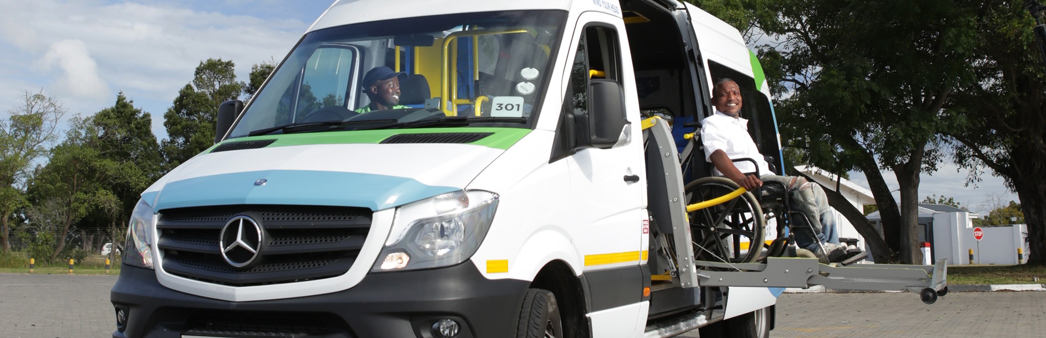 Photo of a passenger in a wheelchair being hoisted into the minibus by an electronic hoist.