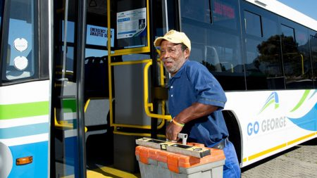 Worker with toolbox taking Go George bus