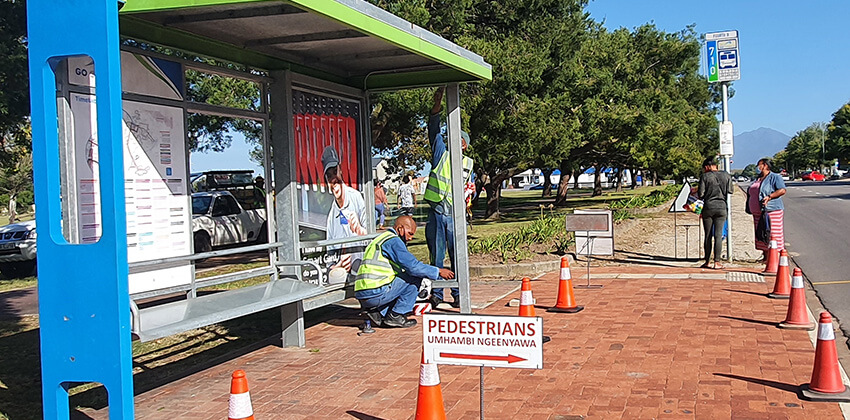 Workmen installing new glass panels on a GO GEORGE bus shelter.