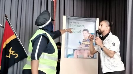 An actor depicting a communication champion scolding an actor depicting a school boy spraying the bus shelter with spray paint.