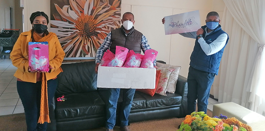 Two men working for GO GEORGE handing over 20 bags containing personal care items for women staying at the Phambili Refuge for women and children. It is received by a lady working at Phambili.
