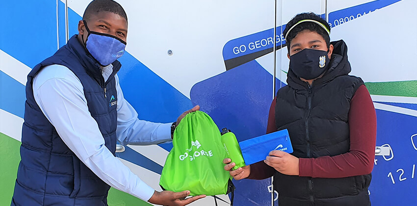 Photo depicting 12-year-old boy receiving a goodie bag with GO GEORGE-branded items as prize for winning the GO GEORGE Youth Month lucky draw. It is handed to him by a young man who is the bus service's Community Liaison Officer.