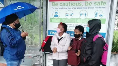 Three school children standing under a bus shelter while a woman in GO GEORGE uniform talks to them. It is raining and the woman is using an umbrella.