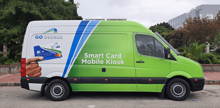 """A minibus branded in the GO GEORGE colours of white, green and blue with a picture of a GO GEORGE Smart Card on the side. The writing on the minibus reads, """"Smart Card Mobile Kiosk""""."""